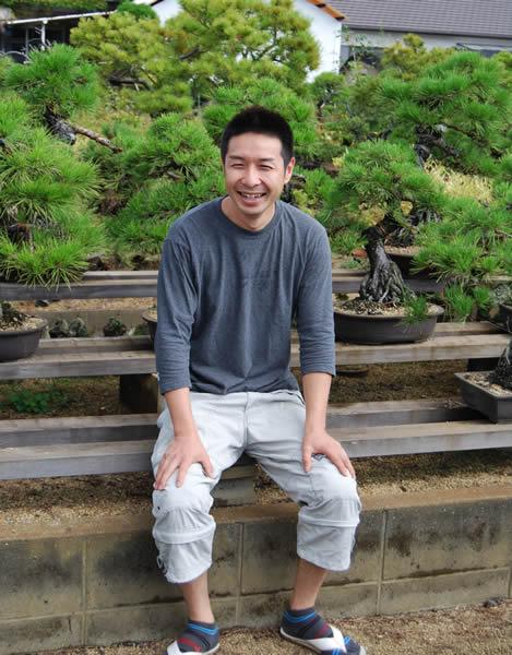 Mitsuo Matsuda smiling in his bonsai garden