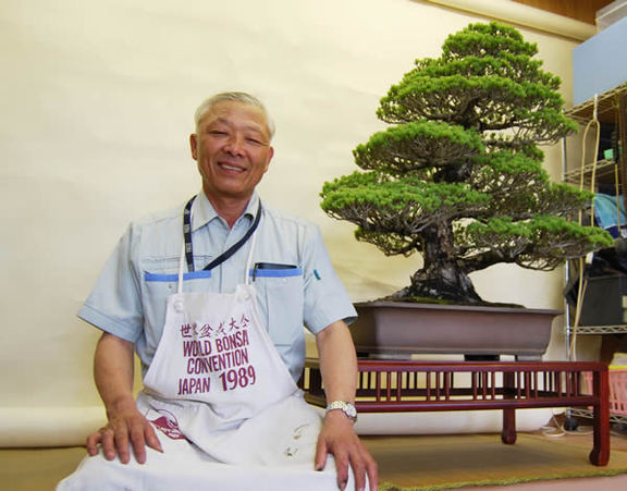 Fumio Ideue with an apron smiles with his products behind.