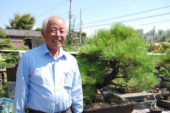 Kunihiro Kandaka smiles in front of bonsai shelves at his garden.