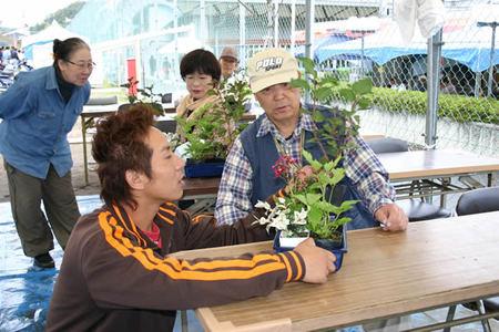 「グリーンフェスタ国分寺」の会場で山野草の寄せ植えを指導する橋本さん(手前)