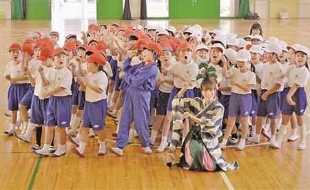 ボンクラの五葉松さんと共に「盆栽たいそう」を踊り、記念写真に納まる児童たち=高松市鬼無町、鬼無小