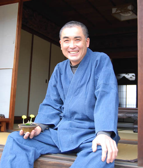 Garden owner Hanazawa poses with a fukujuso (Far East Amur adnis) in a small pot in his hand.