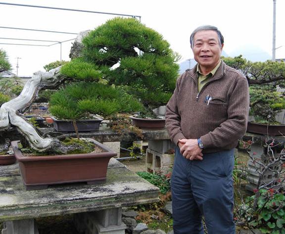 Hiramatsu poses in the bonsai garden.