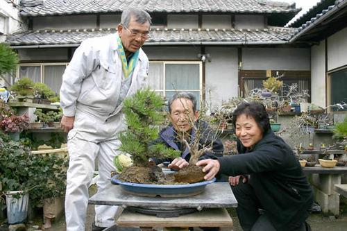 三好さん(中央)に寄せ植え造りを指導する岡田夫妻