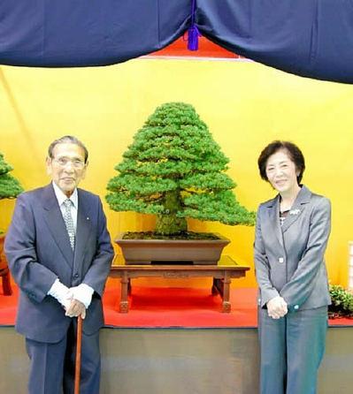 元気な笑顔を見せる生前の岩﨑さん(左)と苗美夫人